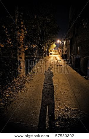 Shadow of a Person in a Dark Urban Alley at Night