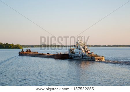 Tug with a barge on Moscow River comes in the evening, Russia