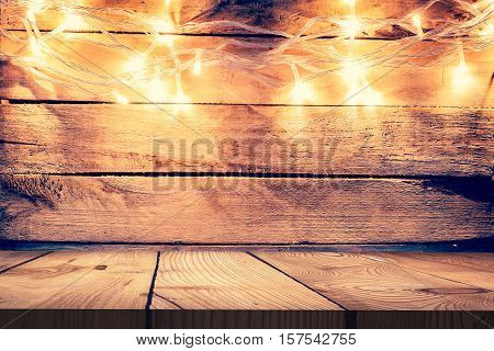 Christmas light on wooden background and wooden table Vintage Christmas Decoration With Lights On Wooden Table Christmas table background with space for product.