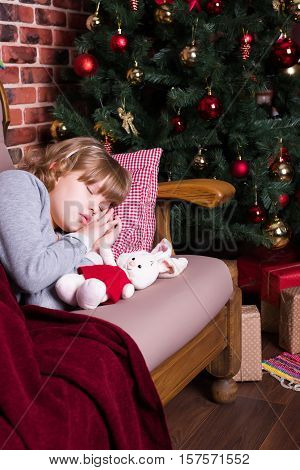 Girl sleeping under a blanket on the sofa near the Christmas tree with gifts
