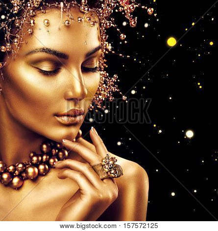 Beauty Fashion model girl with Golden Makeup, Gold skin makeup, hair and jewellery on black background. Gold earrings, ring and necklace. Metallic, glance Fashion art portrait, Hairstyle and make up