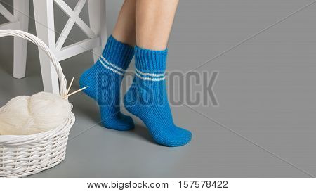 Female legs in blue knitted socks near the basket with yarn and knitting.