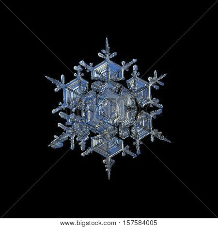 Snowflake isolated on black background. This is closeup photo of real snow crystal: large split plate with many details and glossy, relief surface.