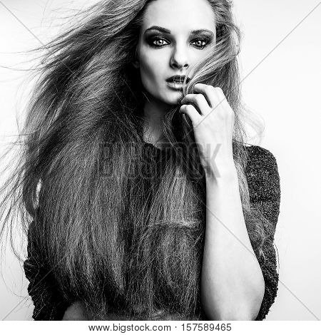 Black-white portrait of beautiful young woman with magnificent long hairs.