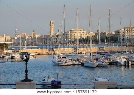BARI, ITALY - JULY 13, 2016: view marina with sailboats, on background Clock Tower of Bari Palace Province