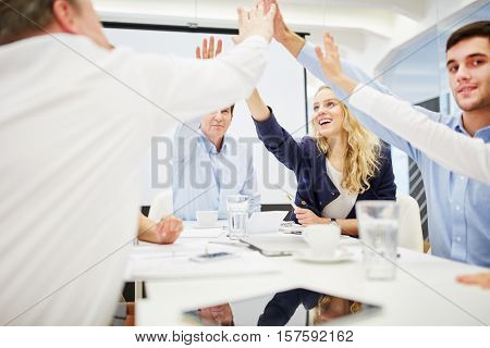Business people give each other a high five and celebrate