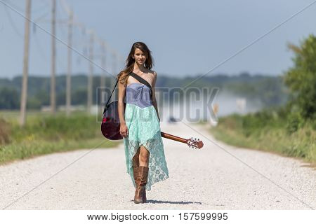 Female walking down a dirt road hitchhiking with a guitar case