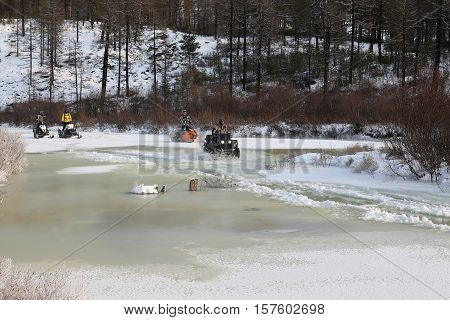 Quad bike (ATV) and snowmobiles will boost ice crust on the river in South Yakutia Russia