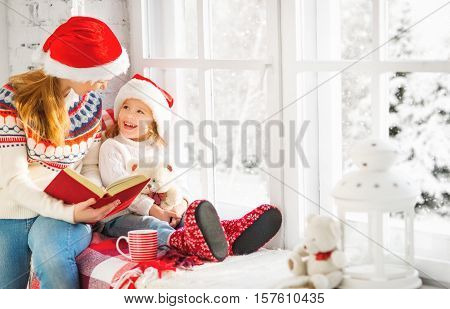 happy family mother and child daughter reading a book on winter window Christmas