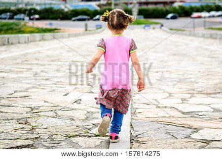 Little girl is running on stone paved promenade at Hercules Tower a Coruna - Spain. Concept of freedom childhood and national heritage.