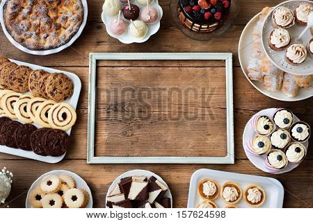 Table with picture frame, cakes, cupcakes, cookies, pie, tarts and cakepops. Studio shot on brown wooden background. Copy space. Flat lay.