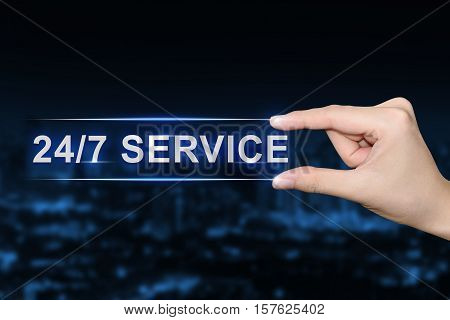 hand pushing 24 hours a day 7 days a week service button on blurred blue background