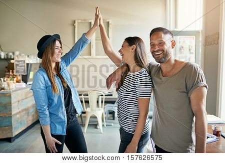 Three people in light room and two women making high five gesture while man smiling away.