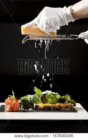 Chef grate cheese on salad with black background