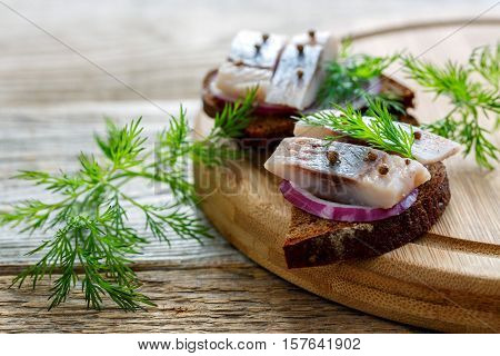 Rye bread with sliced herring with red onion and dill on an old wooden table.