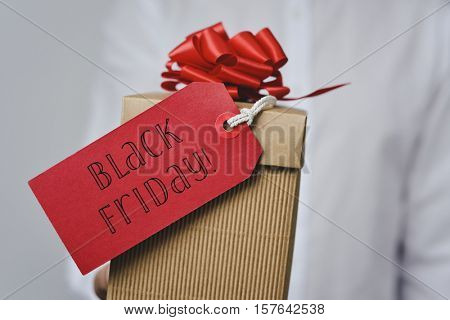 closeup of a young caucasian man in a white shirt holding a gift box with a red label tied to it with the text black friday written in it