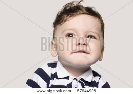Portrait of a cute baby boy looking up making cute faces. Adorable child raising his eyebrow. Happy baby.