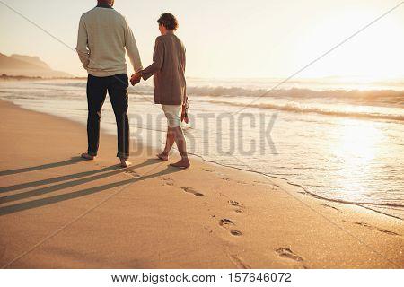 Senior Couple Walking Along The Sea Shore