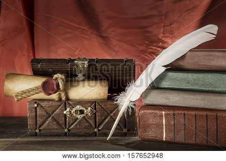 Vintage still life. Feather near sealed scroll in old chest and vintage books on red background.