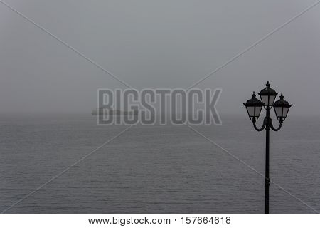 Ship in fog. View from the city's waterfront.