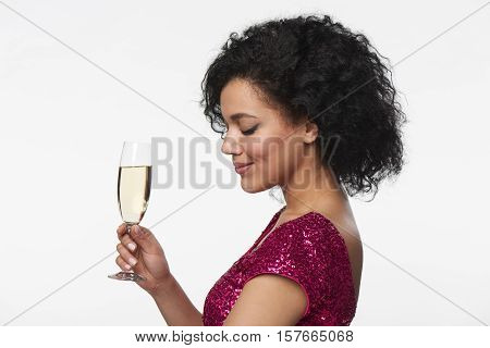 Party, drinks, holidays and celebration concept. Closeup profile portrait of beautiful mixed race caucasian - african american woman in sequined dress holding glass of champagne