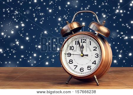 Bronze retro alarm clock at twelve o'clock amid flying snow. Midnight midday. Minutes about New year.