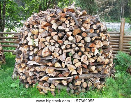 stacked wood for the furnace on a lawn in the form of mountains