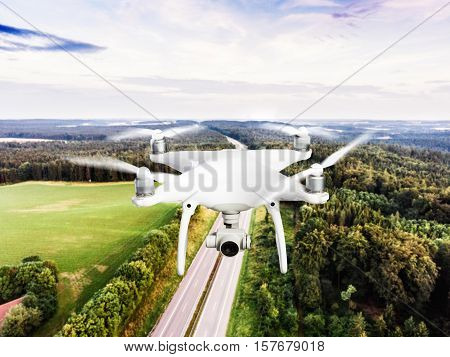 Hovering drone taking pictures of highway in the middle of green forest. Cloudy sky. Netherlands