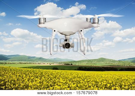 Close up of hovering drone taking pictures of yellow canola field, green hills and blue sky with white clouds