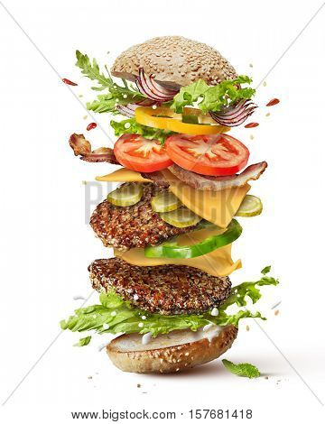 Delicious monster burger with flying ingredients isolated on white background