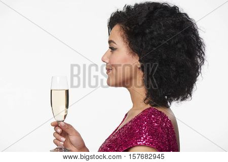 Party, drinks, holidays and celebration concept. Closeup profile portrait of beautiful mixed race caucasian - african american woman in sequined dress holding glass of champagne looking forward