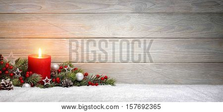 Christmas or Advent wood background with a burning candle on snow decorated with fir branches and ornaments panoramic format with copy space