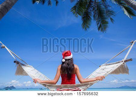 Woman in hammock on tropical beach celebrating Christmas