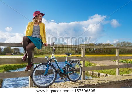 Smiling woman sitting on a wooden fence of the bridge over canal
