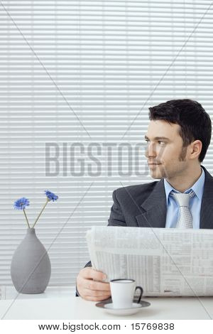 Young businessman having coffee break, sitting at office desk and reading newspaper. Copy space.?