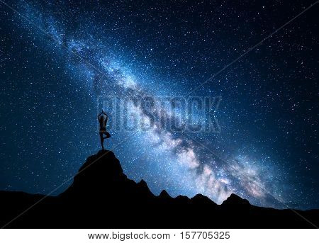 Milky Way with silhouette of a standing woman practicing yoga on the top of mountain. Landscape with meditating girl on the rock against night sky with stars and milky way. Amazing galaxy. Universe