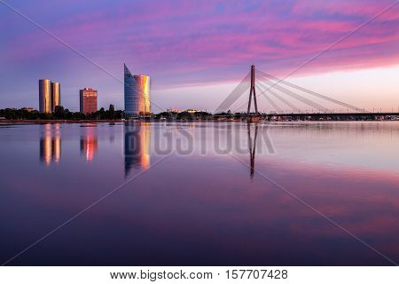 Night view on cable-braced bridge over Daugava river and new buildings on ather bank of it.