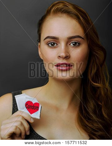 Attractive young woman holding a two condoms looking into the camera. safe sex concept