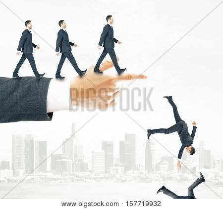 Abstract image of businessmen walking and falling off pointing hand on city background. Risk and failure concept