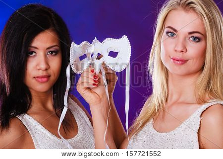 Holidays people and celebration concept. Closeup two women face african and caucasian with white silver carnival masks