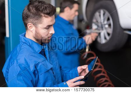 Find out the solution. Handsome confused yong car mechanic using tablet while his colleague changing car wheel in the background