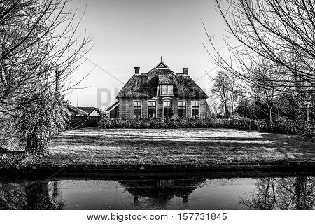 Old cozy house with thatched roof in Giethoorn Netherlands.
