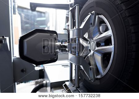 Modern technologies in use. Close up of car tyre fixed in alignment machine clap while being checked