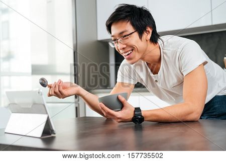 Asian man eating cereal by the table. with tablet. side view
