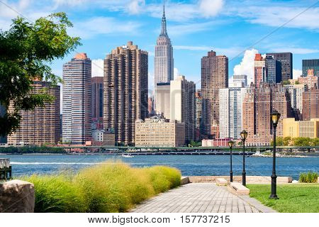 The midtown Manhattan skyline in New York City on a summer day as seen from a beautiful park in Queens
