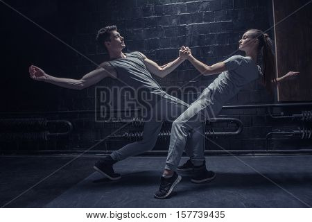 Close interaction and confidence. Involved persistent young dancers performing near the black wall while expressing concentration and interaction in the dancing hall