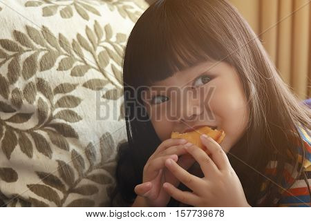 asian adorable child or little girl enjoy eating a custard cake in the room with sunlight from the window