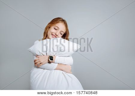 My dear. Positive delighted little girl holdign pillow and embracing it while going to sleep