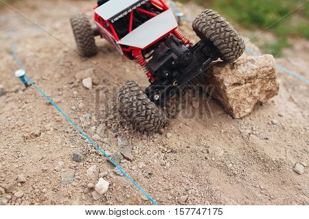 Top view on rc car overcoming rock block on track. Crawler racing on rally trace. Toy truck on landscape road, free space for text