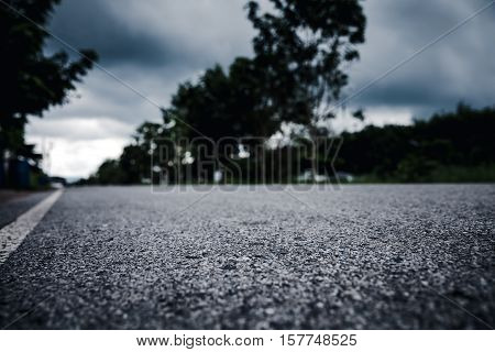 View from below of asphalt road over blurred trees and cloudscape background. Paved road through the forest. Outdoors.